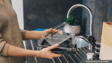 Woman rinsing out a plastic food container